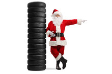 Full Length Portrait Of Santa Claus Leaning On A Pile Of Tires And Pointing To The Side