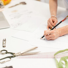 Woman Professional Designer Draws A Sketch On The Workspace With A Set Of Tools For Sewing.  Process Of Creating Fashionable Clothes
