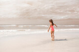 Fototapeta Big Ben - Little girl on a beach with muted color in the ocean and sky
