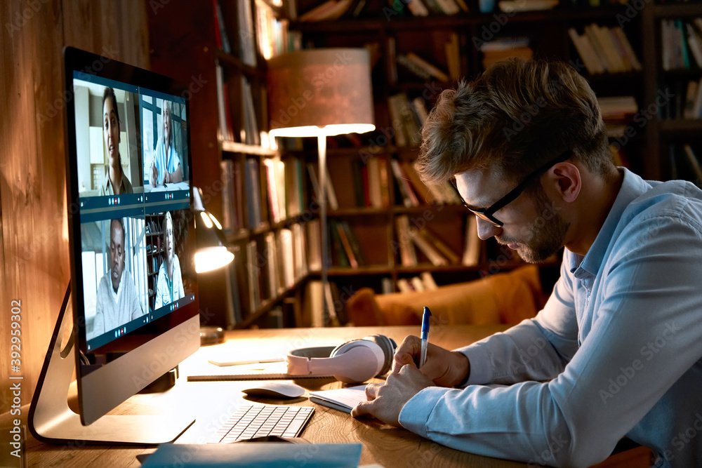 Fototapeta Young business man video conference calling using computer social distance working from home office. Remote male professional videoconferencing by virtual team online web meeting group chat.