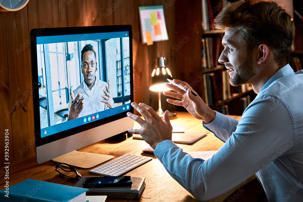 Fototapeta Caucasian business man talking with african male partner coach on video conference call discussing social distance work at virtual remote meeting videoconference chat using pc computer at home office.