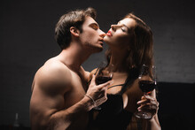 Shirtless Man With Glass Of Wine Kissing Sexy Girlfriend At Home During Evening