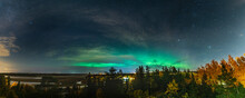 Scenic Aurora Borealis Panorama Photo Across The Whole Horizon, Above Autumn Birch And Pine Tree Forest, City Lights In Swedish Countryside Close To Umea City, Vasterbotten County. Ume River Delta.