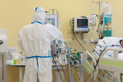 Vászonkép Male nurse with protective coverall clothing in intensive care unit in hospital, where are  treated patients with pneumonia caused by coronavirus covid 19