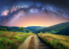 Arched Milky Way Over The Mountain Dirt Road In Summer. Beautiful Night Landscape With Starry Sky, Milky Way Arch, Trail In Mountain Village, Hills, Green Grass And Purple Flowers. Space And Galaxy