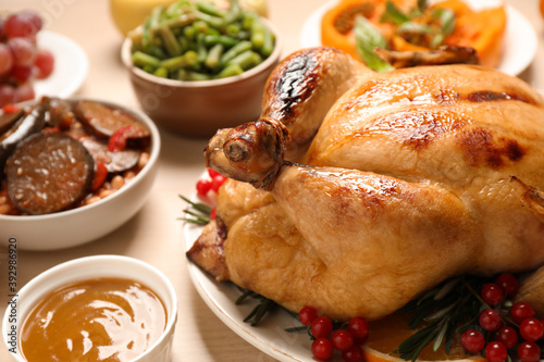 Fototapeta Traditional Thanksgiving day feast with delicious cooked turkey and other seasonal dishes served on wooden table, closeup obraz