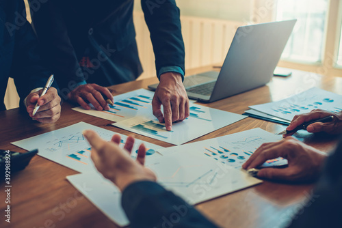 Fototapeta Business people gather to analyze marketing and investment information and pointing to financial data chart at meeting. obraz