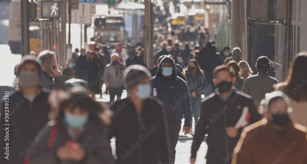 Fototapeta Crowd of people walking street wearing masks