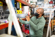 Craftsman In Protective Mask Selects Plastic Plumbing Pipes In A Hardware Store