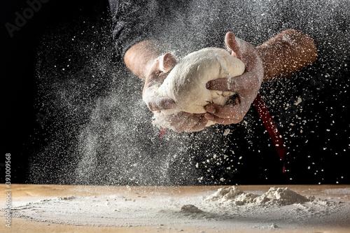 Carta da parati Hands of baker kneading dough isolated on black background