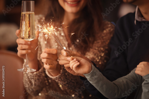 Happy family with sparklers and champagne celebrating Christmas at home