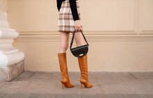 Closeup Female Legs In Red High Heel Boots With Black Handbag. Fashion Street Outfit
