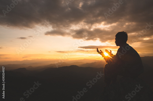Silhouette of young  man hands open palm up worship and praying to god  at sunrise, Christian Religion concept background Fototapet