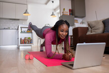 Young African America Woman At Home Doing Exercise In Front Of Open Laptop, Repeating Instructions By Professional Online Fitness Trainer.