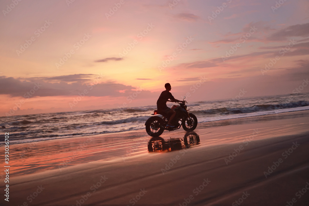 Fototapeta Man And Motorcycle On Ocean Beach At Beautiful Tropical Sunset. Biker's Silhouette On Motorbike On Sandy Coast Near Sea In Bali, Indonesia.