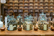 Traditional Chinese Pharmacy Shop. Ancient Herbs Pharmacy Cabinet Wooden Drawers In Background