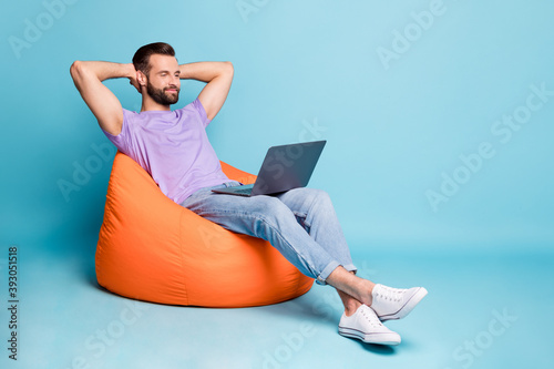 Full length body size photo of bearded programmer chilling during break in orange beanbag isolated on vivid blue color background