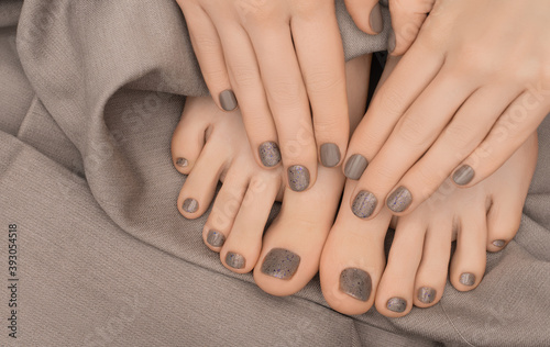 Female hands and feet with brown nail design Wallpaper Mural