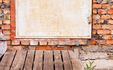 Metal, Slightly Rusty Entrance Door To The Ground Floor With A Red Fire Brick Masonry. Selective Focus.