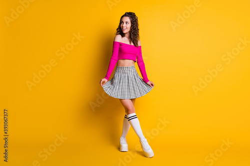 Fototapeta Full body photo of nice feminine wavy lady woman look side empty space wear pink off shoulders top short checkered skirt white long socks shoes isolated yellow color background obraz