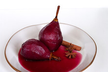 Fresh Pears Poached In Red Wine With Cinnamon On White Plate, Italian Kitchen. Glazed Fruit.