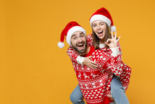 Blinking Young Santa Couple Friends Man Woman In Sweater Christmas Hat Giving Piggyback Ride To Joyful, Sit On Back Showing OK Gesture Isolated On Yellow Background. Happy New Year Holiday Concept.