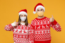 Young Santa Couple Friends Man Woman In Sweater Christmas Hat Face Mask To Safe From Coronavirus Covid-19 Showing Thumbs Up Isolated On Yellow Background. Happy New Year Celebration Holiday Concept.