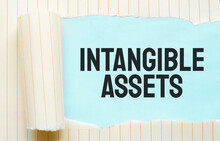 The Text Intangible Assets Appearing Behind Torn White Paper