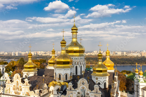 Fotografiet Beautiful yellow and gold domes of the Orthodox Church against the background of the blue sky and the city