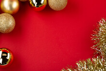 Many Golden Christmas Baubles And Glitter On Red Backdrop. Selective Focus - Shallow Depth Of Field.