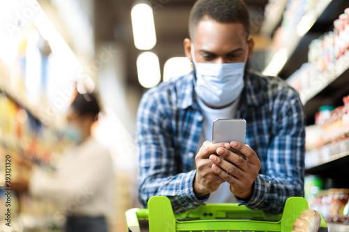 Fotografia, Obraz Black Man With Smartphone Shopping Food In Supermarket Wearing Mask