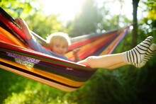 Cute Little Blond Caucasian Boy Having Fun With Multicolored Hammock In Backyard Or Outdoor Playground. Summer Active Leisure For Kids. Child Swinging And Relaxing In Hammock.