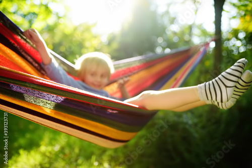 Obraz Cute little blond caucasian boy having fun with multicolored hammock in backyard or outdoor playground. Summer active leisure for kids. Child swinging and relaxing in hammock. - fototapety do salonu