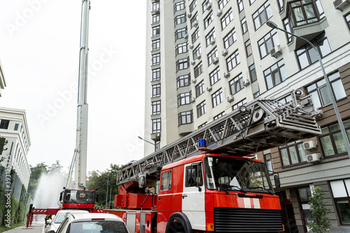 Canvas-taulu Many fire engine trucks with ladder and safety equipment at accident in highrise tower residential apartment or office building in city center