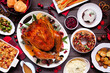 canvas print picture Traditional Christmas turkey dinner. Top view table scene on a dark wood background. Turkey, potatoes and sides, dressing, fruit cake and plum pudding.