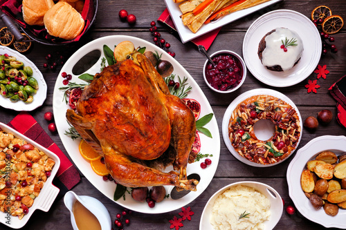Traditional Christmas turkey dinner. Top view table scene on a dark wood background. Turkey, potatoes and sides, dressing, fruit cake and plum pudding.