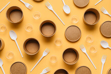 High Angle Of Cardboard Containers With Plastic Forks And Spoons Arranged With Small Plastic Cups For Takeaway Food Service On Orange Table