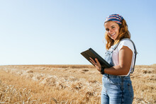 Side View Of Positive Female Farmer In Overalls Standing In Wheat Field In Countryside And Browsing Tablet While Looking At Camera
