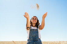 Low Angle Of Delighted Female Tossing Up Wheat Grain While Standing In Agricultural Field In Sunny Day In Village