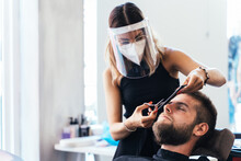 Professional Female Barber In Protective Mask And Face Shield Cutting Beard On Male Customer With Scissors While Working In Modern Barbershop During Coronavirus