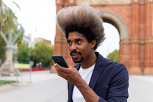 Young Black Man In A Suit Standing On The Street Talking On The Mobile Phone