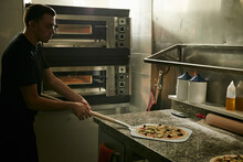 Side View Of Male Chef With Metal Shovel Taking Traditional Italian Raw Pizza Prepared For Baking From Marble Tabletop Into A Oven For Baking In Restaurant Kitchen