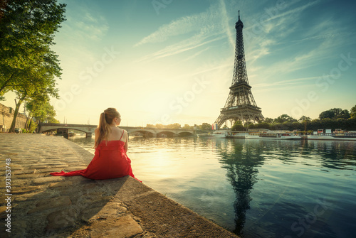 Obraz Young woman in red, looking to Eiffel tower, Paris - fototapety do salonu