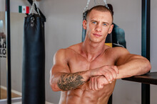 Serious Male Boxer With Tattooed Naked Torso Standing In Sports Center On Background Of Punching Bags And Looking At Camera
