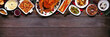 canvas print picture Classic Christmas turkey dinner. Overhead view top border on a dark wood banner background with copy space. Turkey, potatoes and sides, dressing, fruit cake and plum pudding.