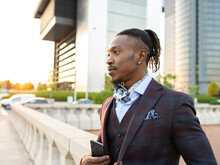 Serious African American Male Entrepreneur Wearing Classy Suit Standing On Street In City Center And Looking Away