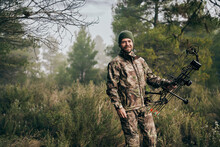Cheerful Man In Camouflage Standing With Compound Bow In Forest And Looking At Camera During Hunting