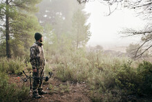Side View Of Man In Camouflage Standing With Compound Bow In Forest And Looking Away During Hunting