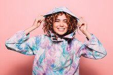 Studio Portrait Of Curly Redhead Girl Over Pink Background. She Is Smiling And Adjusting The Hood Of His Coat