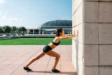 Full Body Side View Of Athletic Female Runner In Activewear Doing Calf Stretch Exercise Against Wall Of Concrete Building During Workout On City Square